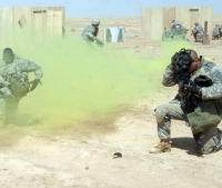 U.S. Army Soldiers put their gas masks on for a simulated chemical attack during a training mission near Camp Ramadi, Iraq