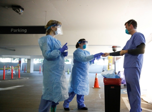 Nurses Becky Barton and Jess White help nurse Jeff Gates take off protective gear after interacting with a patient at a drive-through testing site for coronavirus, flu and RSV at UW Medical Center Northwest in Seattle, Washington, March 9, 2020