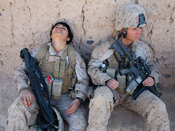 Two sitting soldiers. One is asleep.