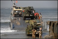 Sailors direct an Army steamroller into the water during JLOTS. Photo Credit: Elizabeth M. Lorge