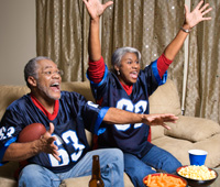 a couple watching football on TV and eating snacks