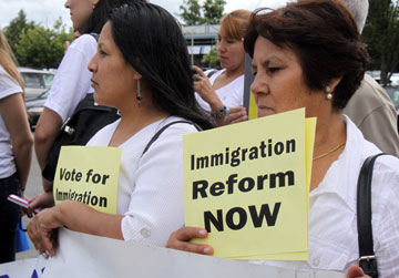 At a rally, two women hold signs calling for immigration reform, photo by longislandwinsFlickr.com