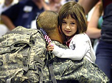 returning soldier hugs daughter, photo courtesy of DoD/Cherie A. Thurlby