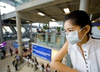 a woman wearing a surgical mask at an airport