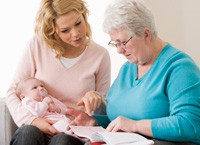 a woman with her baby talking to a home health nurse