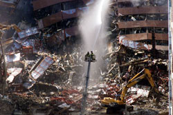 New York City firefighters pour water on the wreckage of 7 World Trade Center in Sept. 2001