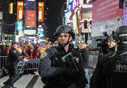 A member of the counterterrorism task force stands guard in Times Square, New York City, December 31, 2016, photo by Stephanie Keith/Reuters