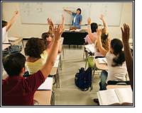 teacher by whiteboard, students with hands raised