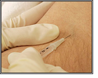 gloved hands administering injection