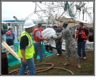 Louisiana National Guard Soldiers help Oil Mop employees load oil booms onto boats/photo courtesy of U.S. Army