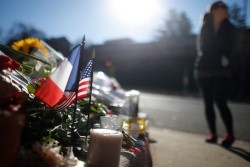 A passerby pauses near a makeshift memorial with U.S. and French flags outside the French embassy in Washington, D.C.