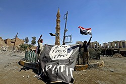 Shi'ite Popular Mobilization Forces (PMF) members hold an Islamic State flag, which they pulled down, during the war between Iraqi army and PMF against Islamic State militants in Tal Afar, Iraq, August 27, 2017, photo by Thaier Al-Sudani/Reuters