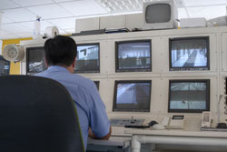 Corrections officer viewing prison monitors