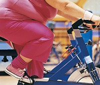 obese woman on exercise bike