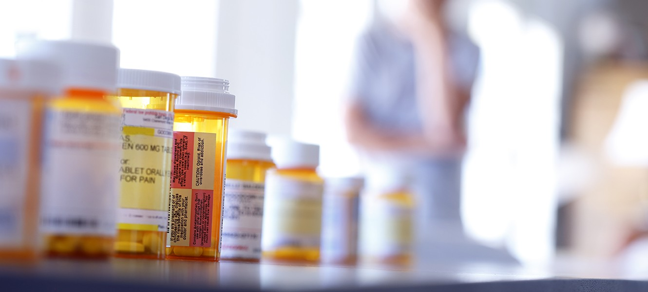 Row of prescription drug bottles in the foreground, man out of focus in the background