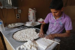 A boy makes pastry at a shop in Darkush town, Syria