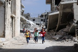 Children run along a damaged street as they celebrate the first day of the Muslim holiday of Eid al-Adha at a rebel-held area in Deraa, Syria, September 1, 2017, photo by Alaa al-Faqir/Reuters