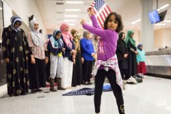A girl dances while women pray at a protest against the Trump administration's travel restriction at Dallas/Fort Worth International Airport, Texas, January 29, 2017Photo by Laura Buckman/Reuters