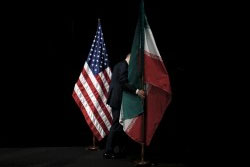 A staff member removes the Iranian flag from the stage after the Iran nuclear talks in Vienna, Austria, July 14, 2015, photo by Carlos Barria/Reuters