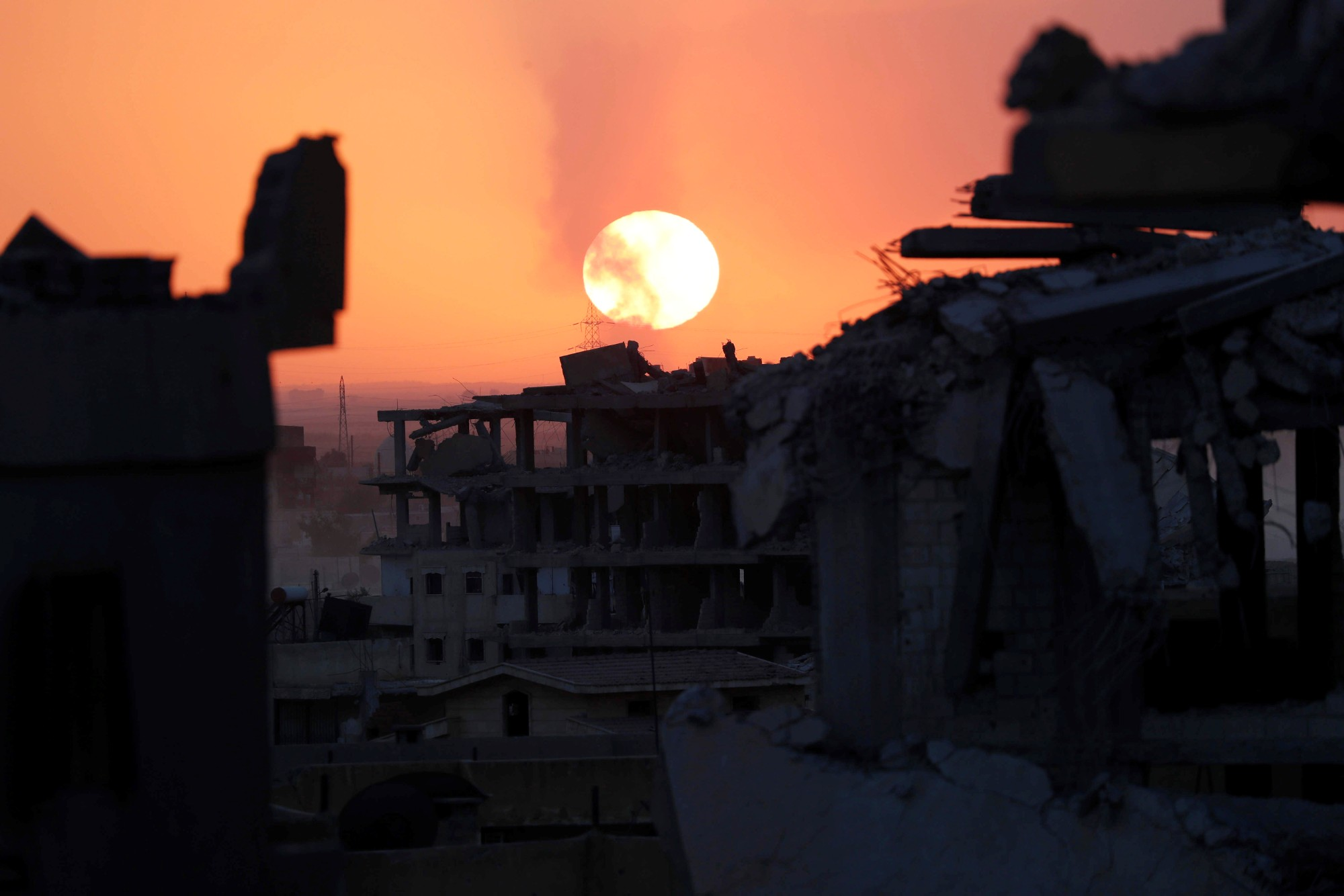 Destroyed buildings during sunset at the frontline in Raqqa, Syria, October 6, 2017, photo by Erik de Castro/Reuters