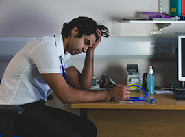 A male doctor sits at his desk, looking unhappy