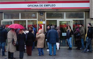 People queue outside an unemployment office in Madrid