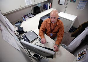 Infection Control Coordinator Rahn Snyder checks data on a computerized infection monitoring system.