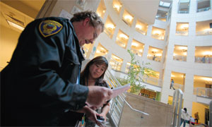 Leah Esguerra, a social worker at the San Francisco Public Library, goes over a list of homeless people who had checked in there with grounds patrolman Paul Little.