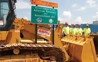 Construction workers await the arrival of President Barack Obama at a highway road project.