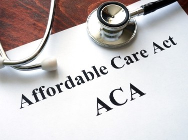 A stethoscope on top of a paper copy of the Affordable Care Act, photo by designer491/Getty Images