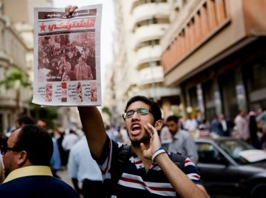 Egyptian man shouting and holding up a newspaper in Cairo on April 20, 2012