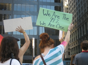"""We are the 99%. We are the one"" sign held at Occupy Wall Street on 10/09/2011"