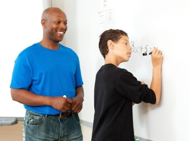 Teacher and middle school student at whiteboard
