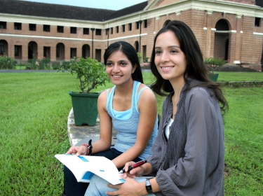 Two students sitting outside on a college campus