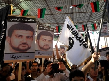 People hold posters of senior al Qaeda figure Abu Anas al-Liby during a demonstration over his capture by U.S. authorities