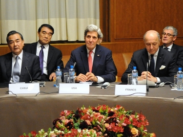 U.S. Secretary of State John Kerry sits between Chinese Foreign Minister Wang Yi and French Foreign Minister Laurent Fabius at the United Nations Headquarters after the P5+1 member nations concluded a nuclear deal with Iran in Geneva, Switzerland, on November 24, 2013.