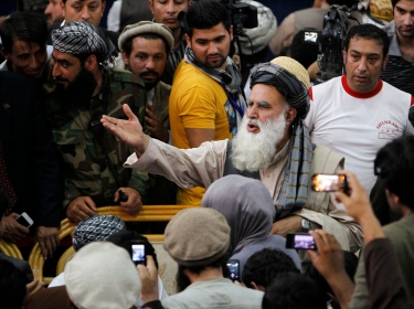 Afghan Mujahideen leader Abdul Rassoul Sayyaf talks with his supporters before registering as a candidate for the 2014 Afghan presidential election