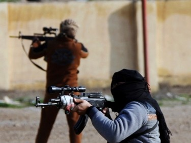 Masked Sunni Muslim gunmen take up positions with their weapons during a patrol in the city of Falluja