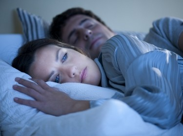 woman with insomnia next to sleeping partner