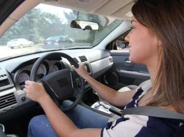 A teenage girl, as seen behind the wheel of a car.