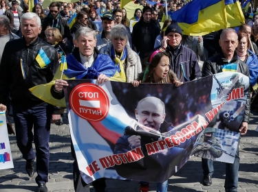 "People rally against the annexation of Crimea by Russia, in Odessa, Ukraine. The banner with a portrait of Putin reads: ""Will not let aggressor to our house."""