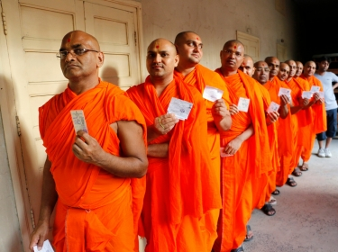 Hindu saints stand in line to cast their votes at a polling station in the western Indian city of Ahmedabad April 30, 2014