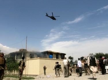 A NATO helicopter flies overhead as smoke rises from the site of a suicide attack in Jalalabad province May 12, 2014. Taliban militants launched a wave of attacks across Afghanistan on Monday, the first day of their declared summer offensive