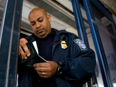 Customs and Border Protection officer Ballard inspects a motorist's passport at the San Ysidro border crossing between Mexico and the U.S. in San Ysidro, California
