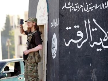 A militant Islamist fighter films his fellow fighters in a parade in Syria's northern Raqqa province, June 30, 2014