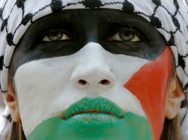 A demonstrator, her face painted in the colors of the Palestinian flag, outside the Israeli Embassy in London, July 26, 2014