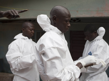 A burial team wearing protective clothing prepares to enter the home a person suspected of having died from Ebola in Freetown, Sierra Leone, September 28, 2014