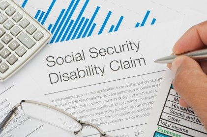 Social Security Disability claim form, pen, calculator