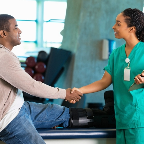 A physical therapist greeting a patient in a hospital rehab gym, photo by asiseeit/iStock