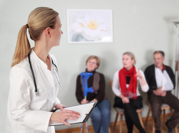 Doctor with a clipboard and patients in a waiting room, photo by RioPatuca Images/Fotolia